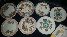 Seven plates laid out with the cats' Christmas Dinners on them