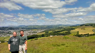 Richard and I under a blue sky with fluffy clouds, Kendal in the midground and the mountains of Cumbria in the background